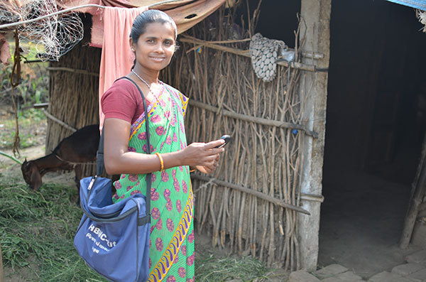 ASHA smiling and holding her smartphone as she enters the home of a patient in rural India.