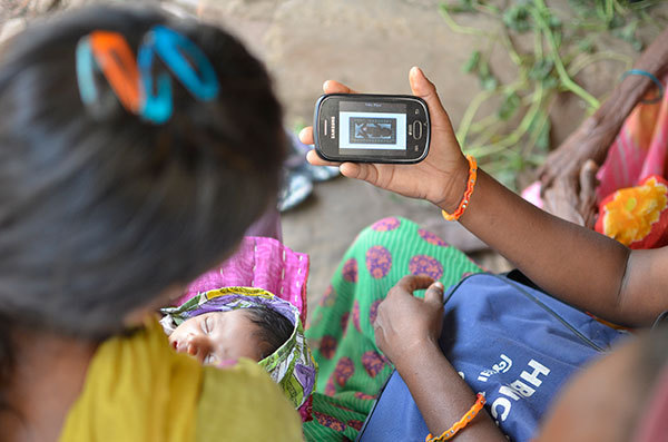 An ASHA shares a view of her smartphone and the ImTeCHO app with a young mother and her baby.