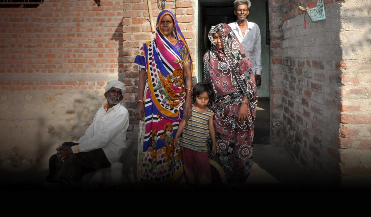 A family from Gujarat,  India, posing in front of their home and their new indoor toilet.