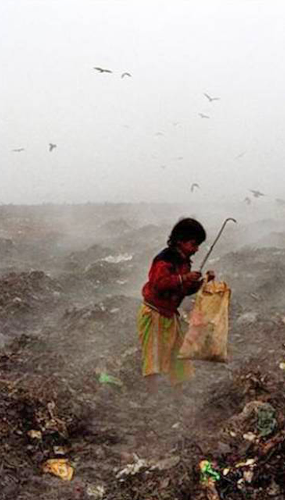 Child searching through dump site.