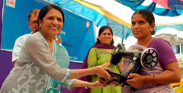 Woman accepting her sewing machine after completion of 12 weeks vocational training.